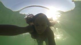 Η αρκετά νέα ευτυχής γυναίκα κολυμπά υποβρύχιο στην τροπική θάλασσα μέσω του ήλιου κίνηση αργή 1920x1080 απόθεμα βίντεο