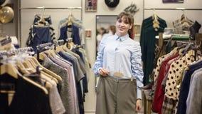 Η αρκετά νέα ευτυχής γυναίκα προσπαθεί στο γκρίζο παντελόνι μπροστά από τη κάμερα σε ένα κατάστημα αλλά τη λήψη ιματισμού του μακ απόθεμα βίντεο