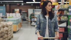 Η αρκετά νέα κυρία περπατά μέσω του διαδρόμου στην υπεραγορά με το κάρρο αγορών εξετάζοντας τα ράφια με τα προϊόντα, υπάλληλοι απόθεμα βίντεο