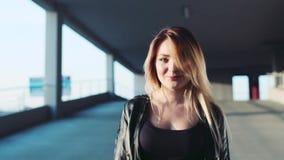 Η αρκετά ξανθή γυναίκα περπατά κάτω από το χώρο στάθμευσης σε ένα φωτεινό φως του ήλιου, κοιτάζει στη κάμερα και χαμογελά γοητευτ φιλμ μικρού μήκους