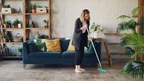 Η αρκετά ξανθή νοικοκυρά κάνει τα οικιακά που το ξύλινο πάτωμα στον όμορφο επίπεδο καθαρισμό κάτω από τον καναπέ Το κορίτσι είναι φιλμ μικρού μήκους