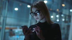 Η αρκετά ξανθός-μαλλιαρή νέα γυναίκα στα γυαλιά με το μαύρο πλαίσιο και τα σκοτεινά ενδύματα είναι στην οδό βραδιού Είναι πλησίον φιλμ μικρού μήκους