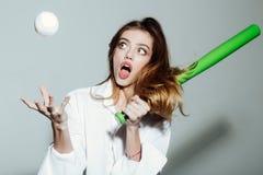 Η αρκετά προκλητική γυναίκα με μακρυμάλλη κρατά το πράσινο ρόπαλο του μπέιζμπολ Στοκ Εικόνες