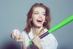 Η αρκετά προκλητική γυναίκα με μακρυμάλλη κρατά το πράσινο ρόπαλο του μπέιζμπολ Στοκ φωτογραφία με δικαίωμα ελεύθερης χρήσης