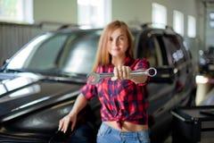 Η αρκετά προκλητική γυναίκα brunette στο ελεγχμένο πουκάμισο παρουσιάζει γαλλικό κλειδί Μακροεντολή θαμπάδων Στοκ Εικόνες
