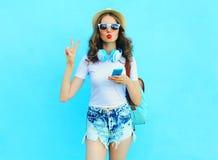 Η αρκετά δροσερή γυναίκα ακούει μουσική και χρησιμοποίηση του smartphone πέρα από το ζωηρόχρωμο μπλε Στοκ Φωτογραφία