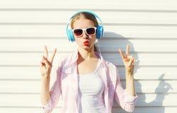 Η αρκετά δροσερή γυναίκα ακούει τη μουσική στα ακουστικά πέρα από το λευκό Στοκ εικόνα με δικαίωμα ελεύθερης χρήσης