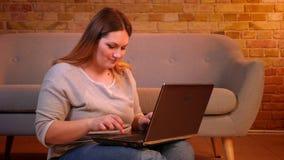 Η αρκετά υπέρβαρη επιχειρηματίας κάθεται στη δακτυλογράφηση πατωμάτων smilingly στο lap-top που ικανοποιεί με την εργασία στο άνε φιλμ μικρού μήκους