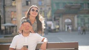 Η αρκετά όμορφη γυναίκα στα γυαλιά ηλίου κλείνει τα μάτια για τη συνεδρίαση φίλων της στον πάγκο στο τετράγωνο πόλεων κατά τη διά φιλμ μικρού μήκους