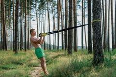 Η αρσενική άριστη κατάρτιση αθλητών trx, καθαρός αέρας το καλοκαίρι φύσης στο πάρκο, αισθάνεται τη δύναμή σας, κίνητρο, ολόκληρο Στοκ Φωτογραφίες