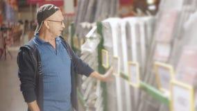 Η αρσενική υπεραγορά κατασκευής ο αγοραστής επιλέγει τη σκάλα για τους φιλμ μικρού μήκους
