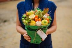 Η αρχική ασυνήθιστη εδώδιμη ανθοδέσμη λαχανικών και φρούτων με την κάρτα στα χέρια γυναικών Στοκ εικόνες με δικαίωμα ελεύθερης χρήσης