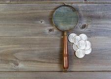 Η ασημένια συλλογή νομισμάτων δολαρίων και ο στρογγυλός τρύγος ενισχύουν το γυαλί επάνω Στοκ εικόνα με δικαίωμα ελεύθερης χρήσης