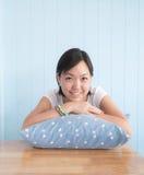 Η ασιατική γυναίκα έβαλε το χέρι σε ένα μπλε μαξιλάρι και ένα χαμόγελο polkadot στοκ εικόνες