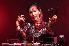 Η ασιατική γυναίκα γιατρών χημείας με την κόκκινη μόδα τόνου αποτελεί τη φαντασία Στοκ Εικόνα