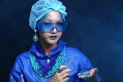 Η ασιατική γυναίκα γιατρών χημείας με την μπλε μόδα τόνου αποτελεί fanc Στοκ φωτογραφίες με δικαίωμα ελεύθερης χρήσης