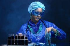Η ασιατική γυναίκα γιατρών χημείας με την μπλε μόδα τόνου αποτελεί fanc Στοκ Φωτογραφία