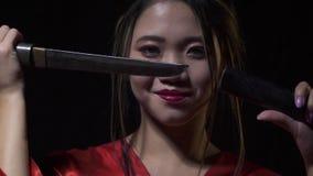 Η ασιατική γυναίκα εμφανίζεται από το σκοτάδι βγάζοντας ένα στιλέτο με ένα χαμόγελο απόθεμα βίντεο