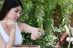 Η ασιατική γυναίκα κάθεται στον υπαίθριο καφέ νέος θηλυκός ενήλικος με φυσικό Στοκ εικόνες με δικαίωμα ελεύθερης χρήσης