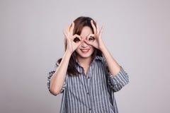Η ασιατική γυναίκα κάνει το αστείο διπλό ΕΝΤΑΞΕΙ σημάδι ως γυαλιά Στοκ Φωτογραφίες