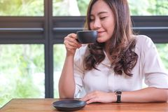 Η ασιατική γυναίκα κλείνει τα μάτια της που μυρίζουν και που πίνουν τον καυτό καφέ με το αίσθημα καλή στον καφέ σοφιτών Στοκ Φωτογραφίες