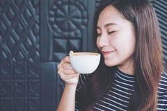 Η ασιατική γυναίκα κλείνει τα μάτια της που μυρίζουν και που πίνουν τον καυτό καφέ με το αίσθημα καλή στον καφέ Στοκ Εικόνα