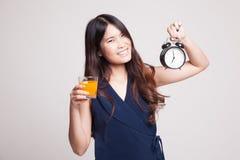 Η ασιατική γυναίκα με ένα ρολόι πίνει το χυμό από πορτοκάλι Στοκ φωτογραφίες με δικαίωμα ελεύθερης χρήσης