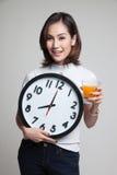 Η ασιατική γυναίκα με ένα ρολόι πίνει το χυμό από πορτοκάλι Στοκ εικόνα με δικαίωμα ελεύθερης χρήσης