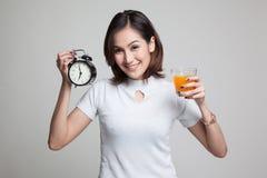 Η ασιατική γυναίκα με ένα ρολόι πίνει το χυμό από πορτοκάλι Στοκ Εικόνες