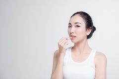 Η ασιατική γυναίκα με το όμορφο skinface αποτελεί μη, καθαρό καλλυντικό χειλικό κραγιόν στο άσπρο υπόβαθρο Στοκ φωτογραφία με δικαίωμα ελεύθερης χρήσης