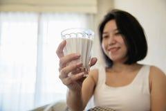 Η ασιατική γυναίκα πίνει το γάλα μετά από ξυπνήστε στη συνεδρίαση πρωινού σε ένα κρεβάτι στοκ εικόνα