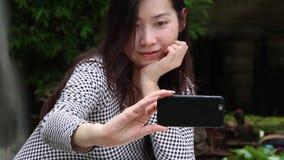 Η ασιατική γυναίκα παίρνει selfie τη φωτογραφία στον κήπο απόθεμα βίντεο