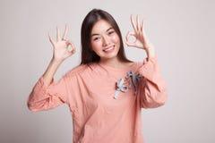 Η ασιατική γυναίκα παρουσιάζει το διπλά ΕΝΤΑΞΕΙ σημάδι και χαμόγελο χεριών Στοκ φωτογραφία με δικαίωμα ελεύθερης χρήσης