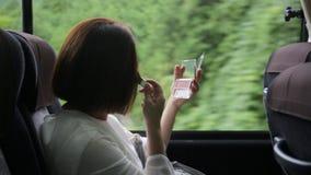 Η ασιατική γυναίκα που εφαρμόζει την ομορφιά αποτελεί στο λεωφορείο, κίνηση απόθεμα βίντεο