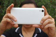 Η ασιατική γυναίκα που κρατά και που χρησιμοποιεί το έξυπνο τηλέφωνο παρουσιάζει πίσω πλευρά στοκ εικόνες