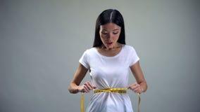Η ασιατική γυναίκα που μετρά τη μέση με την ταινία, επιθυμεί να χάσει το βάρος, κίνδυνος ανορεξίας στοκ φωτογραφίες