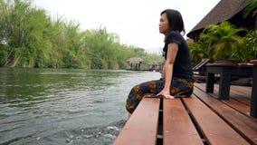 Η ασιατική γυναίκα χαλαρώνει από τη συνεδρίαση ποταμών στην άκρη ενός ξύλινου λιμενοβραχίονα απόθεμα βίντεο