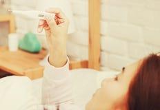 Η ασιατική γυναίκα χρησιμοποιεί ένα θερμόμετρο για να ανιχνεύσει τον πυρετό στοκ εικόνα με δικαίωμα ελεύθερης χρήσης