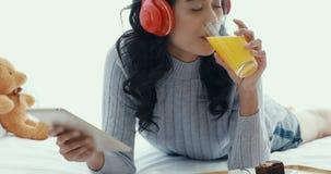 Η ασιατική γυναίκα χρησιμοποιεί την ταμπλέτα και το χυμό από πορτοκάλι κατανάλωσης