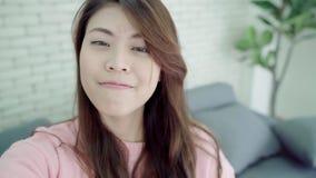 Η ασιατική γυναίκα blogger που χρησιμοποιεί το βίντεο καταγραφής smartphone vlog στο καθιστικό στο σπίτι, θηλυκό απολαμβάνει την  απόθεμα βίντεο