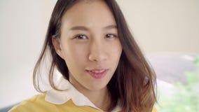 Η ασιατική γυναίκα blogger που χρησιμοποιεί το βίντεο καταγραφής smartphone vlog στο καθιστικό στο σπίτι, θηλυκό απολαμβάνει την  φιλμ μικρού μήκους