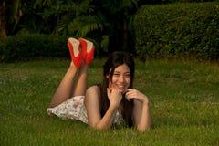 Η ασιατική γυναίκα Smilling αρκετά θέτει να βρεθεί σε έναν χορτοτάπητα στο πάρκο Στοκ φωτογραφίες με δικαίωμα ελεύθερης χρήσης