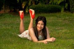 Η ασιατική γυναίκα Smilling αρκετά θέτει να βρεθεί σε έναν χορτοτάπητα στο πάρκο Στοκ Φωτογραφίες