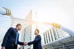Η ασιατική επιχείρηση δύο έχει τη χειραψία με την οικοδόμηση και το backgro πόλεων Στοκ Φωτογραφίες
