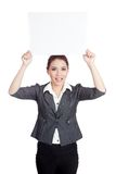 Η ασιατική επιχειρηματίας ευτυχής παρουσιάζει κενό σημάδι άνω του χ Στοκ Φωτογραφίες