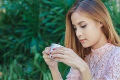 Η ασιατική επιχειρησιακή γυναίκα απασχολείται και πίνει στον καφέ σε υπαίθριο Στοκ Φωτογραφίες