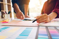 Η ασιατική εργασία σχεδιαστών στο γραφείο του και επιλέγει τα χρώματα togeth Στοκ φωτογραφία με δικαίωμα ελεύθερης χρήσης