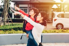 Η ασιατική ευτυχής μητέρα που φέρνει το παιδί της, το σημείο παιδιών διανέμει στοκ εικόνα