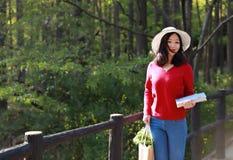 Η ασιατική κινεζική όμορφη γυναίκα κρατά ένα βιβλίο και τα λουλούδια φορούν ένα καπέλο στη φύση την άνοιξη υπαίθρια Στοκ Εικόνες