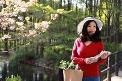 Η ασιατική κινεζική όμορφη γυναίκα κρατά ένα βιβλίο και τα λουλούδια φορούν ένα καπέλο στη φύση την άνοιξη υπαίθρια Στοκ Φωτογραφίες
